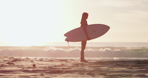 Young, beautiful, blonde surfer woman stands with her surfboard on the beach with the sea and surf in the background in dawn light, in Australia. Medium shot in 4K on a RED camera