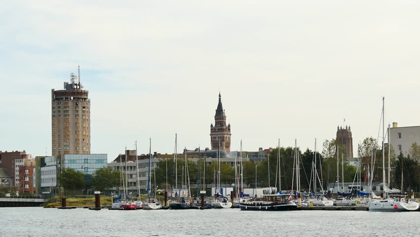 View of the city of Dunkirk, in the north of France. In the foreground, there is the Dunkerque marina. In the background, the famous towers of the city, included the city belfry of the city hall.