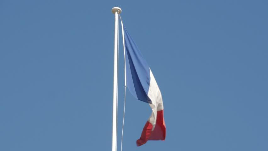 Paris, France - September 2018. Flag of France -  Tricolour Flag flying above Gare du Nord Rail Station terminus, Rue de Dunkerque, 10th arrondissement, Paris, France