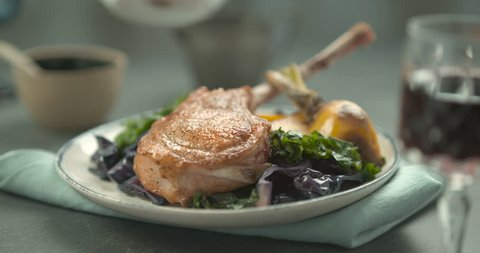 Pink sauce poured on rack of lamb in faience plate with salad and yellow turnip, on a blue towel, with a glass of red wine in the foreground. Close shot in slow motion in 4K on a Phantom Flex camera.
