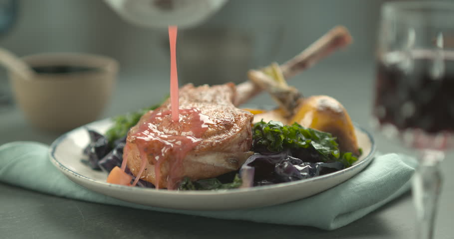 Pink sauce poured on rack of lamb in faience plate with salad and yellow turnip. Chef's Table and cooking show inspired footage. Close shot in slow motion in 4K on a Phantom Flex camera.