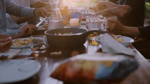 Group of friends or family enjoy dinner outside during backyard barbecue in park. Common table simply decorated with plates, water and beer kegs. Happy times in summer, friendship and sharing concept