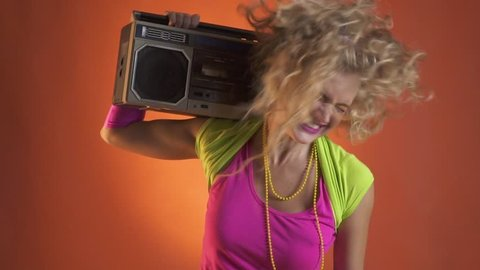 Young blonde woman having fun dancing with the boombox, retro style