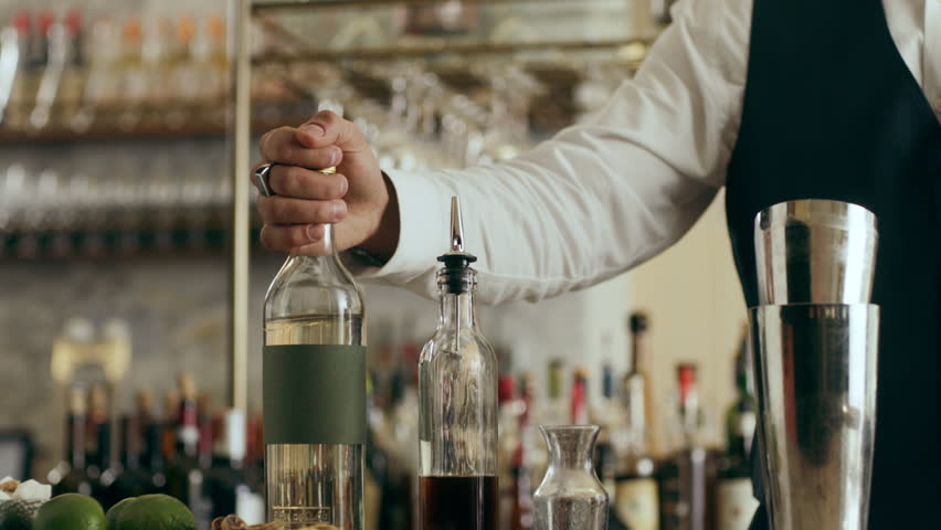 Professional flair artist flipping a bottle in the air before pouring it into shaker making classic Daiquiri cocktail in a beautiful modern trendy bar. Close shot on a RED camera. #1019195848