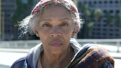 Portrait of an elderly African American homeless woman on the street.