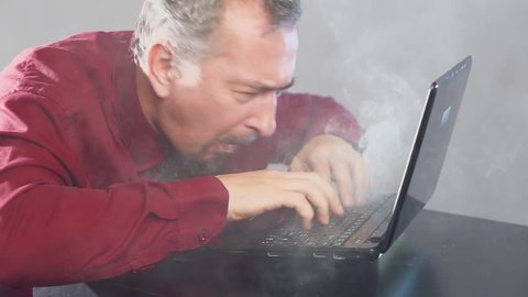 Crazy fanatical businessman working on a burning computer. Accountant report. Cryptocurrencies.
