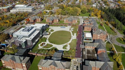Aerial shot descending upon college campus commons during a sunny autumn morning.