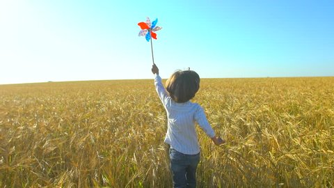 little boy running with toy wind turbine in hand at summer sunset nature outdoors Wheat field Happy kid child playing having fun pinwheel Happiness vacation childhood children happy family holiday