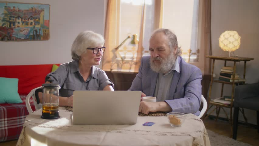 Retired couple doing online shopping at home. Senior woman and mature man sitting at table with laptop computer and credit card and talking. Slow motion. | Shutterstock HD Video #1019339278