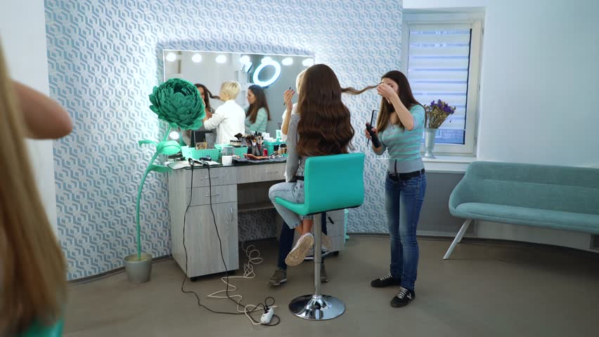 panning shot of beauty salon girls doing professional makeup and hairstyle for young women. people, cosmetics, care, lifestyle, style concept