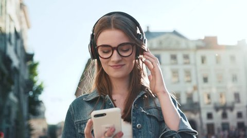 Attractive young woman with glasses listening to music in headphone use smartphone at city walk sunset look around smile portrait close up slow motion