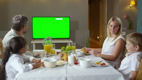 Caucasian family having breakfast in the kitchen: mother and father eating fried eggs and croissants, talking with children and watching TV with green chroma key screen