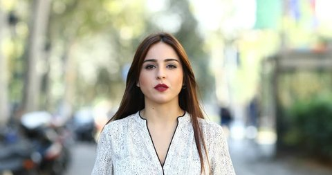 Front view of a relaxed serious woman talking at camera in the street