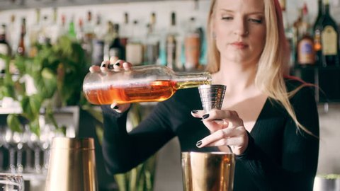 Shot of a concentrated barmaid pouring shots of alcohol into a cocktail shaker in a fancy bar with soft interior lighting. Medium shot on 4k RED camera.