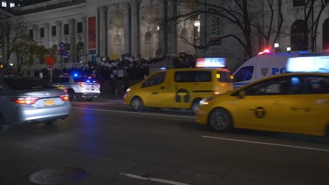 NEW YORK CITY - NOVEMBER 2016: Police cars with emergency lights parked on 5th Avenue and anti Bannon protesters in front of the New York Public Library in New York City, USA.