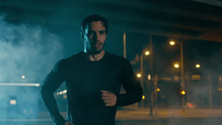 Sweating Athletic Muscular Young Man in Sports Outfit Jogging in a Street Filled With Smoke. He is Running in an Evening Urban Environment Under a Brindge with Cars in the Background.