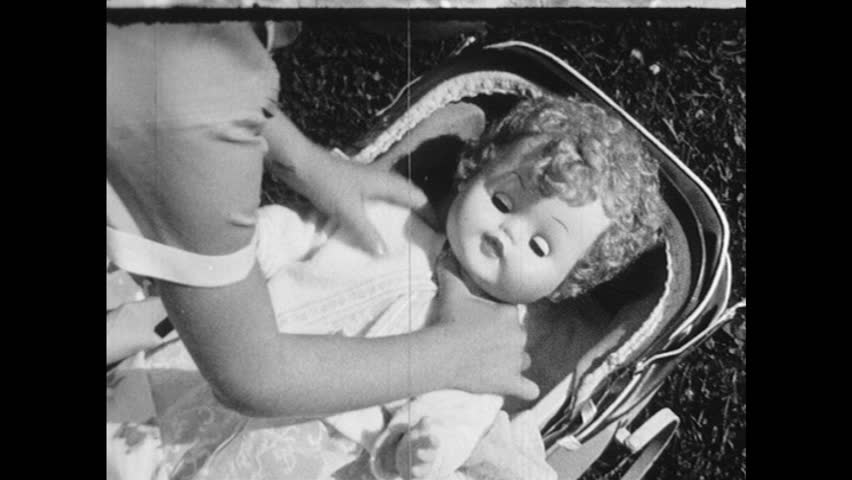 1960s: UNITED STATES: Girl puts doll in crib. Boy plays with Meccano set. Balloon pops. Girl with hula hoop. Boy hits ball with baseball bat. Boy blows balloon. Archery board