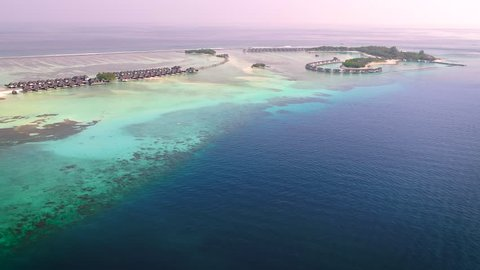 4K Aerial Video of a Small Tropical Island in Maldives Island. Palm Tree on the Sandbank. Top View of the Tropical Lagoon Sea Surface. Luxury 5 Star Resort Hotel. Water Bungalow hut Relaxing Holiday