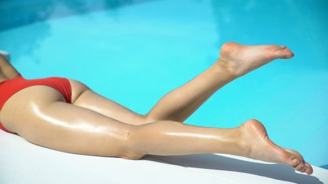 Sexy woman legs with clean shaved soft skin near swimming pool, summer suntan