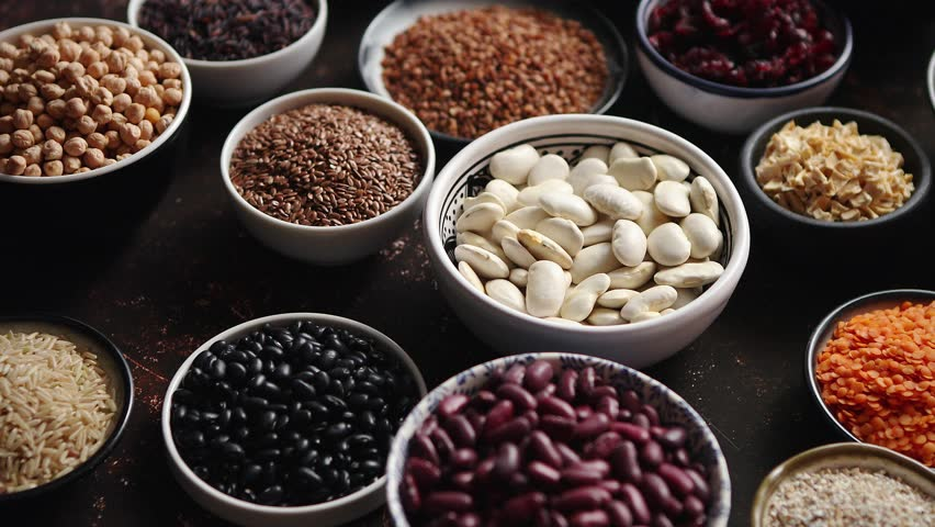 Various superfoods in smal bowls on dark rusty background. Superfood as rice, lentil, beans, peas, goji, flaxseed, buckwheat, couscous, chickpeas Above view Flat lay