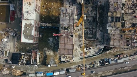 Aerial view of construction workers work on top of the building at construction site - Drone is rising up