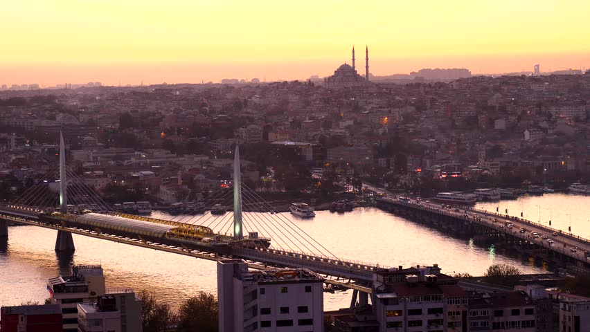 ISTANBUL - NOVEMBER 02, 2017: Overhead view of Golden horn crossed by Halic Metro and Ataturk bridges, evening twilight time after sunset. Fatih mosque seen standing out at skyline, bright yellow sky | Shutterstock HD Video #1019685358