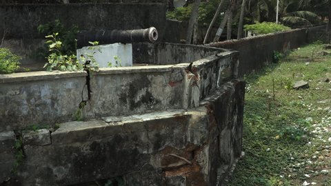A mid steady shot  on a shinny day capturing , dark , disfigured, discolored, moldy weathered , cracking walls of fort Emanuel gunnery,  Kochi Beach, Kerala. Atop white concrete block, remains, bla