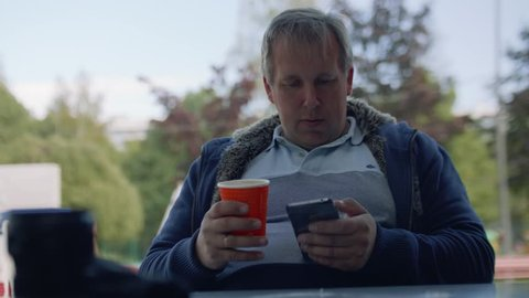 Man in t-shirt with paper cup of coffee surches internet in his smartphone