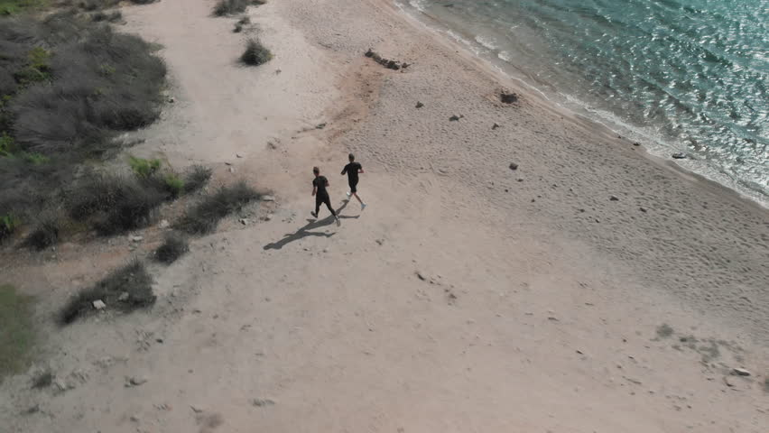 Aerial View of Two Athletic Men Running on the Beach  | Shutterstock HD Video #1019746858