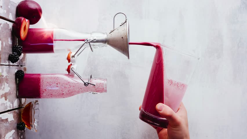 Cinemagraph. Pouring fresh berry smoothie. Vertical format