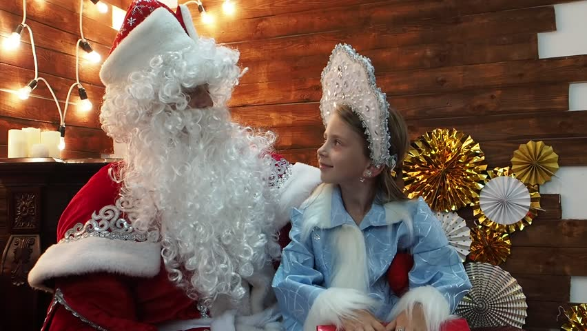 Father Frost Santa Claus tells something to the little girl Snegurochka. New Year's Christmas fairy tale characters communicate sitting at a fireplace.