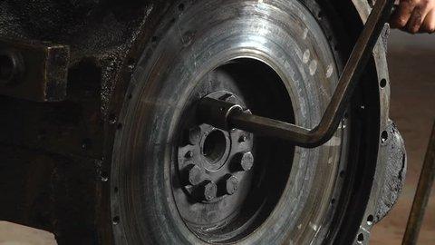 Car engine flywheel. The mechanic unscrews the key flywheel. In the workshop remove the flywheel from the car engine.