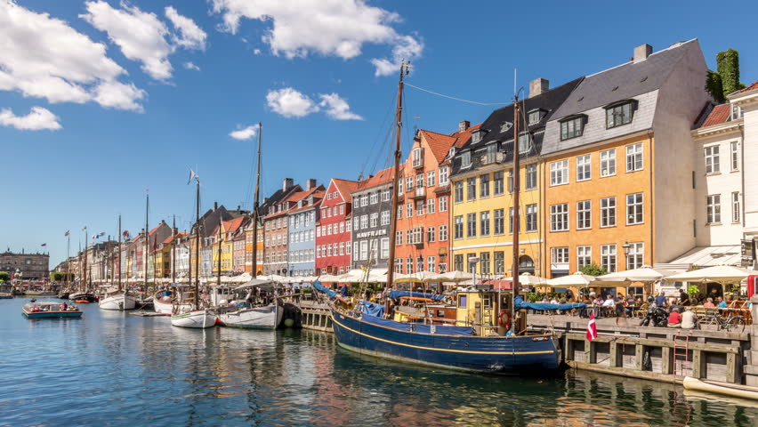 Nyhavn canal (New Harbour), a 17th-century waterfront and entertainment district in Copenhagen, Denmark. Colorful houses facades and sailing boats. White clouds move across blue sky. Time lapse video. | Shutterstock HD Video #1019812078