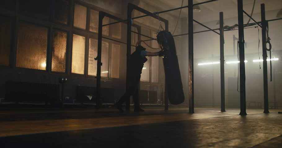 Mid 50s adult male boxer hitting a huge punching bag at a boxing studio alone. 4K UHD | Shutterstock HD Video #1019831008
