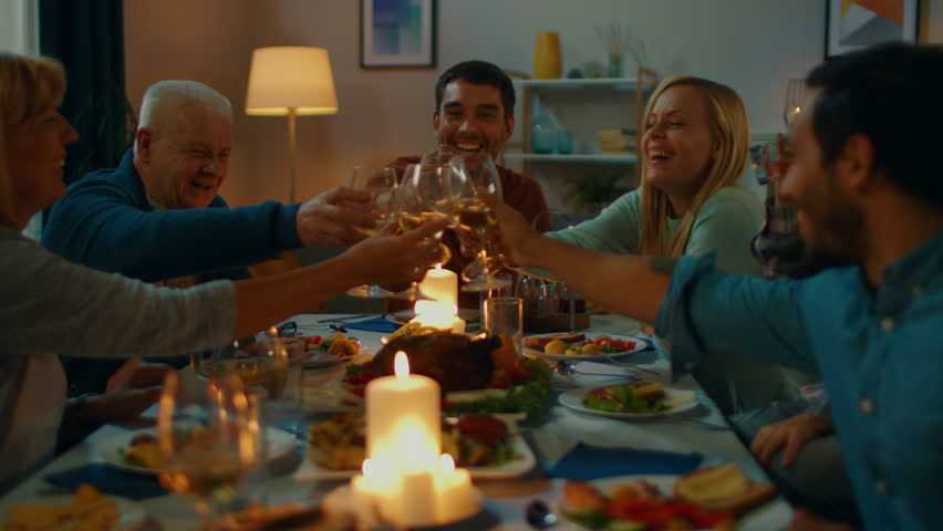Big Family and Friends Dinner Celebration at Home, Diverse Group of Children, Young Adults and Old People Gathered at the Table have Fun Conversation. Clinking Glasses and Making Toast. | Shutterstock HD Video #1019842168