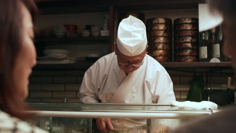 Happy Japanese couple sitting at a sushi bar watching the chef make dinner in small sushi bar with soft interior lighting. Close up shot on 4k RED camera.