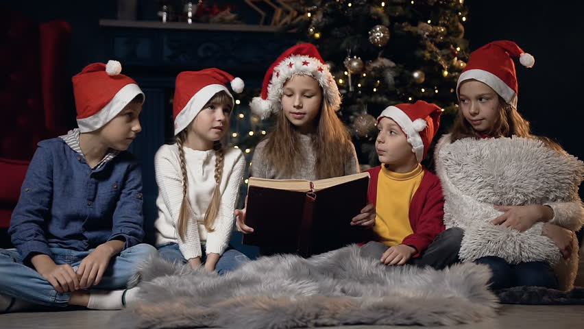 Beautiful smiling kids in stylish sweater in christmas red hat reading interesting history in book sitting near christmas tree in cozy room. | Shutterstock HD Video #1019917828