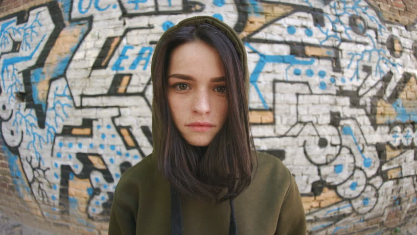 Portrait of serious teen looking at camera. Pretty girl with nice freckles on face against graffiti wall. Street art. Hip-hop culture. Close-up. Deep look. | Shutterstock HD Video #1019928118