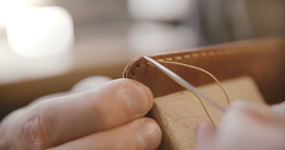 Macro close-up shot of leather sewing process details, hands with needle and strings making a bag on saddler in workshop | Shutterstock HD Video #1019938378
