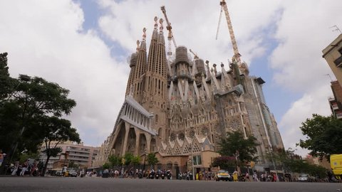 BARCELONA, SPAIN - AUGUST 12, 2018: Famous Barcelona landmark, Sagrada la Familia, still under construction as for August 2018, full height establishing shot. Tourists around building, tower cranes