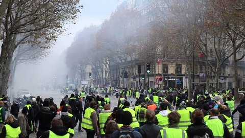 "Paris/France -11.24.2018 Protest ""'Yellow Vests"" (Gilets Jaunes) against the government of Emanuel Macron Place de La Madeleine. Police retaliates and shoots with smoke bombs and tear gas"
