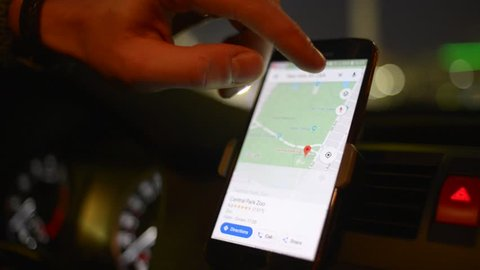 WROCLAW, POLAND - NOVEMBER 23, 2018: Night Driver in New York looks search for a way on Google Maps On Mobile Phone