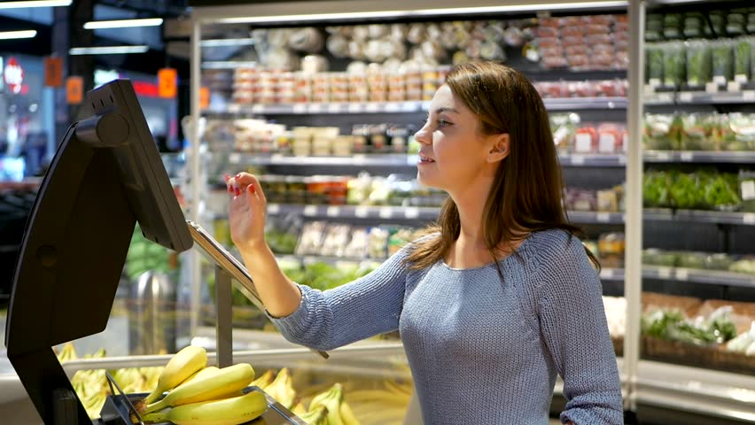 Young girl weighing banana in supermarket. Shopping. Woman weighting banana fruits bio food in vegetable store or supermarket | Shutterstock HD Video #1020014938