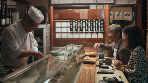 Happy Japanese couple eating sushi and watching while chef cooks in small sushi bar with soft interior lighting. Close up shot on 4k RED camera.