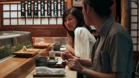 Hungry Japanese couple scarf down sushi while talking with the head chef in small sushi bar with soft interior lighting. Medium close up shot on 4k RED camera.
