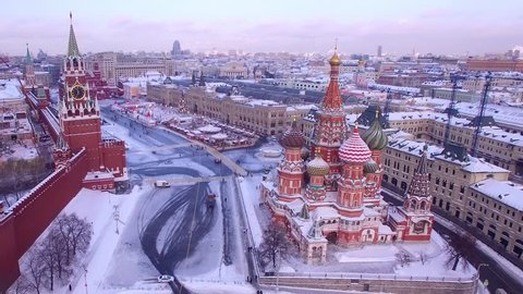 Unique aerial flight Red Square Moscow capital Russia. Winter snow holidays New Year celebration preparation. Saint Basil's Cathedral orthodox colorful church. Happy people walk. Day dramatic mood