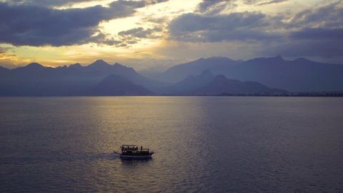 Tourists travelling by small ship in scenic marine background. Beautiful sunset sunny sea water, mountains, cloudy fluffy sky, sailing yacht and  Antalya city landscape. Real time 4k video footage.