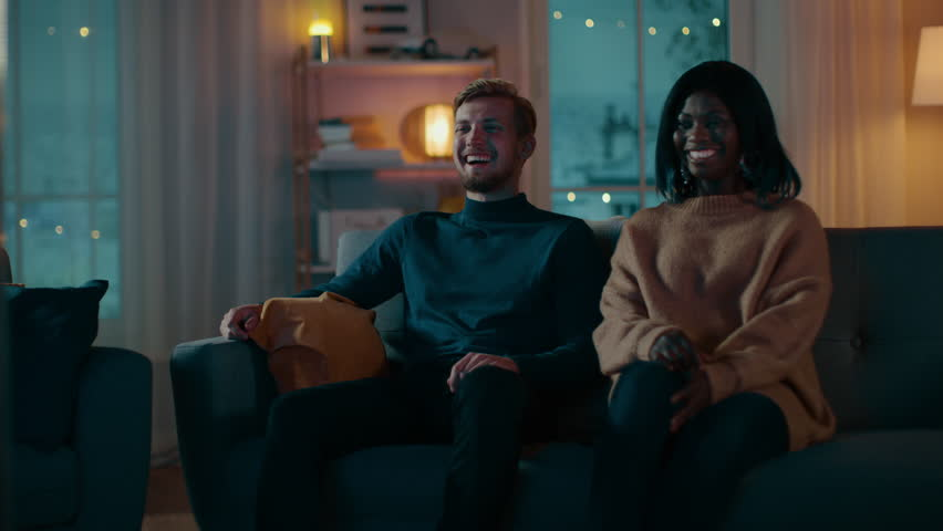 Happy Diverse Young Couple Watching Comedy on TV while Sitting on a Couch, they Laugh and Enjoy Show. Handsome Caucasian Boy and Black Girl in Love Spending Time Together in the Cozy Apartment. | Shutterstock HD Video #1020145168