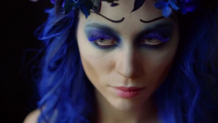 Completion of creative makeup on a woman model combing the built-up blue lashes with a brush | Shutterstock HD Video #1020146218