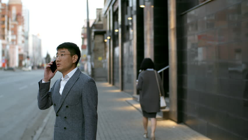 Tilt down shot of Asian man in formal clothes and glasses standing on pavement and discussing work with colleagues on the phone | Shutterstock HD Video #1020151588